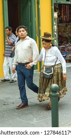 Lima, Peru - 27.12.2018. Couple of man and old woman, people in modern and traditional clothes on the street of Lima, capital Peru, Latin America.