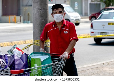 Lima, Peru - April 4 2020: Wong supermarket worker wearing a mask amid coronavirus outbreak in South America. Organizing shopping carts outside a store in COVID-19 times.