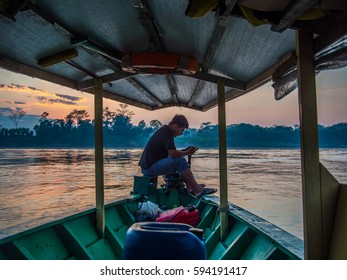 LIMA, PERU - AUGUST 17, 2016: The driver of a boat waits to his passengers on the prow, looking at his cellphone