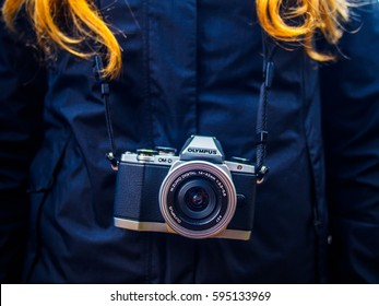 LIMA, PERU - AUGUST 18, 2016: Close-up of a photo camera hanging on the neck of a blonde woman