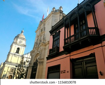 LIMA, PERU - DECEMBER 27, 2016: the wooden balconies of Agua Viva restaurant, with a view of Church of San Pedro's bell/clock tower in the far end