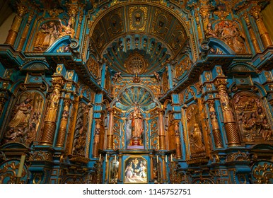 LIMA, PERU - JULY 11, 2018: Interior of a chapel inside the Lima Metropolitan Cathedral with Virgin Mary with baby, a baroque style altar in wood with blue and gold decorations.