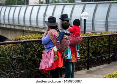 Lima, Peru - July 7 2019: Two peruvian mothers caring their children on their back walking in Miraflores district.