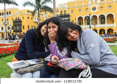 Lima Peru, June 2018: A group of native girls blush when surprised by the photographer while they rest in the Plaza de Armas in the city of Lima, Peru