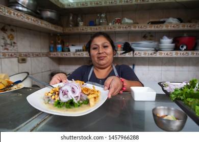 Lima, Lima, Peru, June 9, 2017: Female cook exhibiting a plate of a ceviche