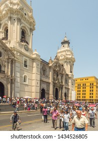 Lima, Peru - March 29, 2018: People with colorful umbrellas on the street of Lima next to Parroquia del Sagrario. Easter time. Maundy Thursday. Plaza de Armas, Peru, South America. Latin America