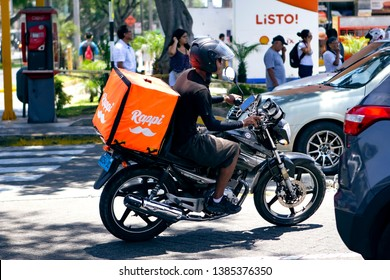 Lima, Peru - March 3 2019: Rappi driver food delivery service riding his motorbike with orange box. Sharing collaborative economy concept in South America.