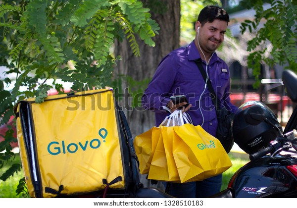 Lima, Peru - March 3 2019: Man smiling with Glovo bags working at food delivery service, standing besides his motorbike. Sharing collaborative economy concept in South America.