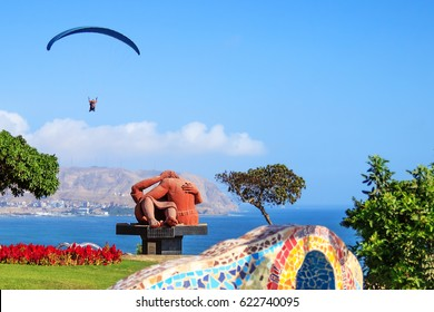 LIMA, PERU – MAY 13, 2014: Paragliding in Miraflores in the Parque del Amor or Park of Love in nice sunny day. Statue El Beso or The Kiss