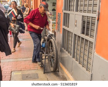 Lima, Peru - May 27, 2016: Man is sharpening the knife on the street of Lima