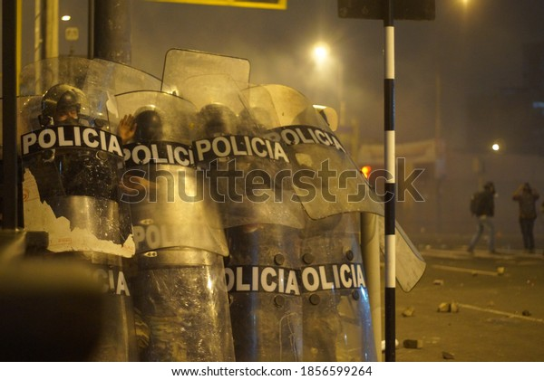 Lima, Peru - November 12, 2020: Polices take cover with their shields during a clash with demonstrators during a protest against the decision of Congress to remove former President Martin Vizcarra.