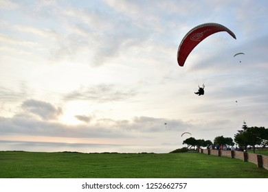 Lima, Peru November 2018 People relaxing in a public garden and paragliders flying  along the coast in Miraflores  a districtin the south of the city.