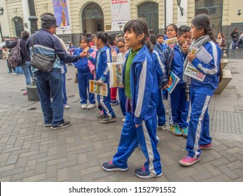Lima, Peru - Sep 23, 2017: Children from the school wearing the uniforms walking  on the street of Lima city. In the background railway station