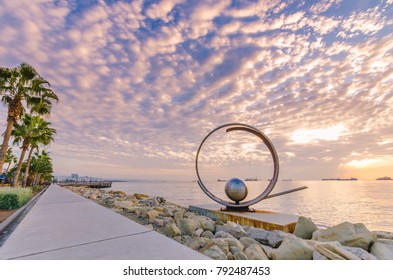 Limassol city, Cyprus - 12/18/2017: Molos Promenade and skyline of coast and sculpture landmark at cloudy sunrise. The boardwalk pier path with palm trees, rocks by the water and the Mediterranean sea