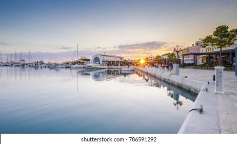 Limassol city, Cyprus - 12/29/2017: Modern commercial area of Marina at sunset, a high end life in newly developed port with docked yachts, restaurants, shops, a landmark for waterfront promenade.