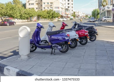 Limassol, Cyprus - April 3, 2018:  Four new Zhen scooters on display on the pavement of a busy main road. Four colours to choose from.
