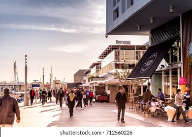 LIMASSOL, CYPRUS - FEBRUARY 18, 2017: People out for a walk along the promenade. Limassol Marina.