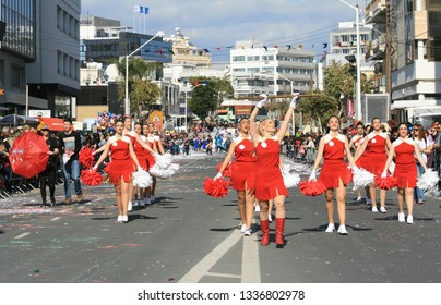 Limassol, Cyprus, March 10th, 2019: Drum majorettes in red costumes with pom-poms marching along Archbishop Makarios III Avenue during Grand Carnival Parade of Annual Limassol Carnival Festival