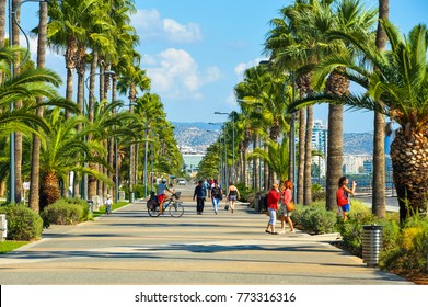 LIMASSOL, CYPRUS - November 06, 2017: People on Molos Promenade, the main walking alley with palm trees