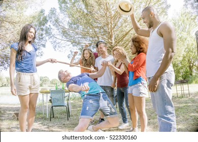 limbo dancing in garden. group of young friends having fun outdoors in park on a bright sunny day dancing limbo and laughing clapping and cheering the winner at competition