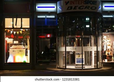 LIMBURG, GERMANY - NOVEMBER 03: Modern shop windows and a glass revolving door of an Intersport sports shop at night on November 03, 2018 in Limburg.
