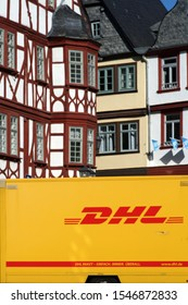 LIMBURG, GERMANY - OCTOBER 12: A parcel of DHL parcel service stands in front of half-timbered houses of the listed Old Town on October 12, 2019 in Limburg.