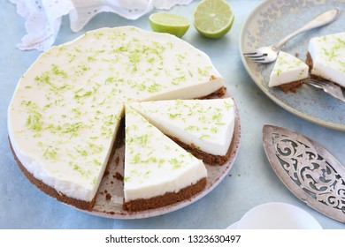 Lime cheesecake and cup of cofee on blue background