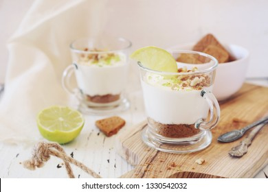 Lime cheesecake in two cups on light background. Toned image