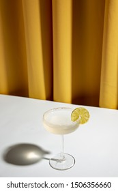 Lime cocktail in a champagne saucer on white desk against yellow curtain