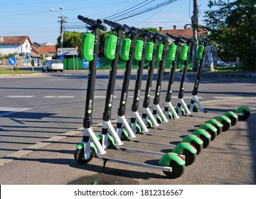 Lime electric scooters parked on the sidewalk in Cluj-Napoca, Romania on September 8, 2020