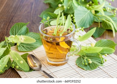 Lime flower tea in glass cup with linden flowers. midicinal remedy.