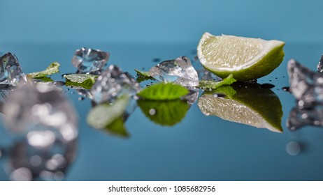 Lime fruit with ice isolated on blue background