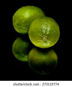 lime fruit on black mirror, isolated
