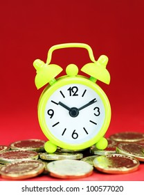 A lime green alarm clock placed on some golden coins with a red background, asking the question how long before your investment matures?