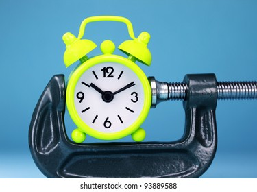 A lime green alarm clock placed in a Grey clamp against a pastel purple background, asking the question do you manage your time effectively