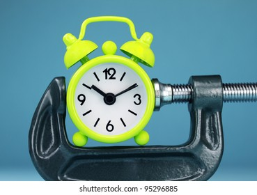 A lime green alarm clock placed in a Grey clamp against a pastel blue background, asking the question do you manage your time effectively.