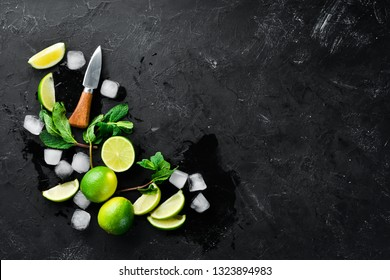 Lime, ice and mint on a black stone background. Top view. Free space for your text.
