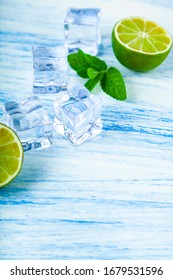 Lime, ice and mint on a blue wooden table.