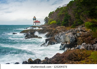 "Lime Kiln Lighthouse. A stormy day on San Juan Island, Washington. Waves crash against the rocky coastline.The long exposure makes the water look ""silky""."