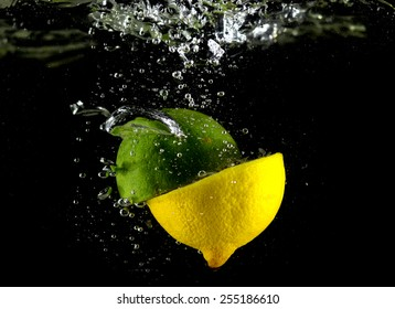 lime and lemon falling in water, lime and lemon in the fall, collision with lime water (on a black background)