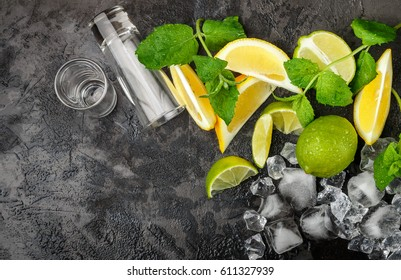 Lime, lemon, mint and crushed ice on a black background. The ingredients for making refreshing drinks and cocktails. Copy space. Selective focus