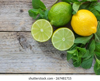 Lime, lemon and mint - Juicy ripe citrus on an old wooden  background. The ingredients for making refreshing drinks and cocktails. Mojito. Selective focus, top view and copy space