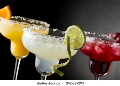 Lime margarita, orange margarita and cherry margarita cocktail mix in salt rimmed glasses garnished with slices of lime, orange and cherries. focus on the lime slice