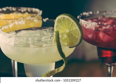 Lime margarita, orange margarita and cherry margarita cocktail mix in salt rimmed glasses garnished with slices of lime, orange and cherries. Selective focus on the lime slice