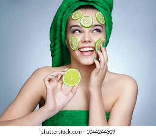 Lime mask. Beautiful girl holding a slice of lime and smiling. Photo of girl with flawless skin in green towels. Skin care and beauty concept