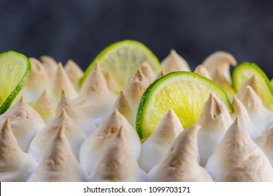 Lime meringue cake with slices of lime with dark background - detail view
