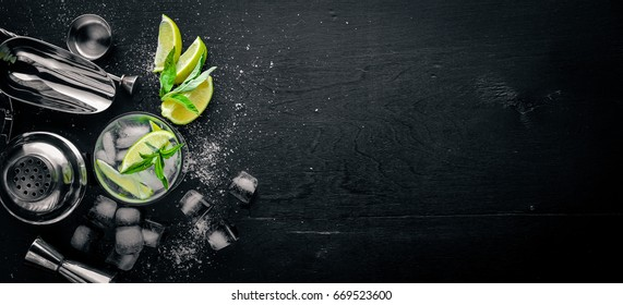 Lime and Mint cocktail, with ice, on a black wooden surface. Top view. Free space.