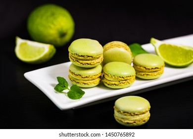 Lime and Mint Flavored Green Macarons Cookies on Black Background. Selective focus.