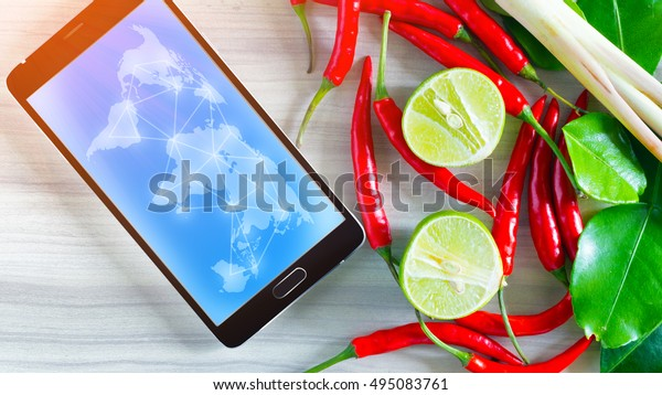 lime, peppers ,chili's ,Lemon grass, phone on wood table,graphic global networks ,export Thai ingredients,food and technology