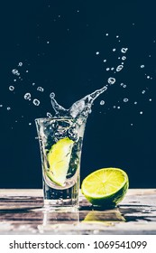 Lime slice falls into a glass with alcohol, gin, tequila, vodka